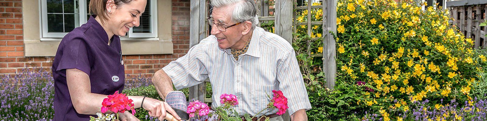 Photograph of care home worker helping elderly man pot some plants